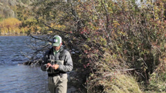 A flyfisherman prepares his rod for flyfishing on an Idaho river Stock Footage