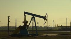 Oil pumpjack, donkey pumper, wind turbine, sunset, oil well pumps, fuel drilling Stock Footage