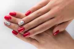 red nails with crystals and hands white background - stock photo