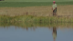 A fly fisherman fishes on a golf course pond Stock Footage