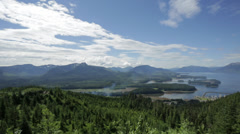 A wide angle shot of green mountains and a bay in Icy Straight, AK Stock Footage