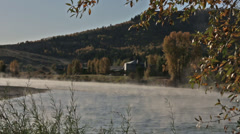 Mist floats over an Idaho river at dawn with a lodge next to shore Stock Footage