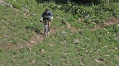 A mountain biker bikes on a rocky, windy mountain trail in Idaho Stock Footage