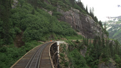 View from rear of train as it passes over bridge and through tunnel in Skagway, - stock footage