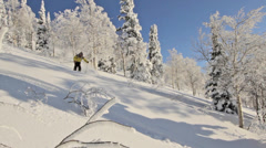 A male skier skis through trees and launches off small natural feature Stock Footage