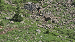 A mountain biker rides through a rocky talus field in Idaho - stock footage