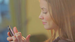 Cute beautiful young lady browsing mobile phone sends messages. click for HD - stock footage