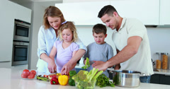 Stock Video Footage of Smiling family preparing a healthy dinner together