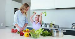Smiling mother and daughter preparing a healthy dinner together Stock Footage
