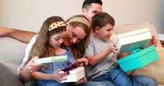 Happy young family sitting on sofa with birthday presents - stock footage