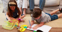 Young siblings doing arts and crafts on the rug while parents look on - stock footage