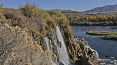 A waterfall flows into an Idaho river Stock Footage