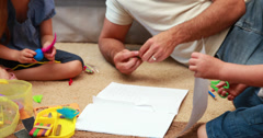 Happy siblings doing arts and crafts on the rug with parents Stock Footage