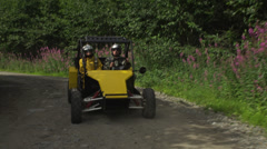 A slow motion shot of a couple driving an off-road vehicle on a dirt road in Stock Footage