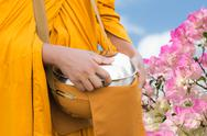 Stock Photo of a buddhist monk carrying an alms bowl