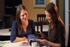 Two female friends read magazine laughing, girls company smile. click for HD - stock footage