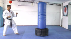 Black belt karate practicing kicking the sandbag Stock Footage