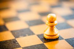 white chess pawn standing on chessboard - stock photo