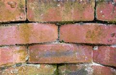 Cracks appearing in cement of red brick retaining wall Stock Photos