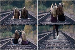 Two girls sitting on railway tracks and show love Stock Photos