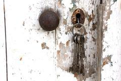 doorknob and bunch of keys in peeling shed door - stock photo
