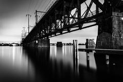 railroad bridge over the susquehanna river at night, in havre de grace, maryl - stock photo