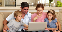 Happy family sitting on the sofa using laptop Stock Footage