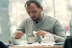 Happy young man adding sugar into tea in cafe NTSC Stock Footage