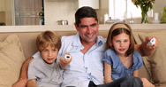 Stock Video Footage of Cute children playing video games with their father on the sofa