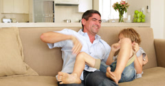 Father and daughter tickling little boy in the couch Stock Footage