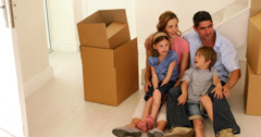 Happy family sitting on floor in their new home - stock footage