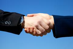 Hand shake between man and woman in front of the sky Stock Photos