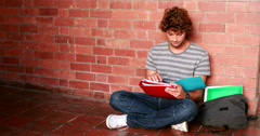 Stock Video Footage of Student sitting against wall reading textbook