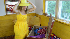 Girl with yellow dress put heavy suitcase on bed yellow hat head Stock Footage