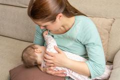 young mother breast feeding her baby at home - stock photo