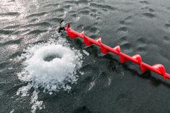 Ice drill and fragile ice - stock photo