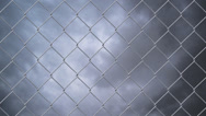Stock Video Footage of Chain link wire fence against cloudy sky time lapse