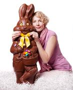 Blond girl adjusting bowtie of a chocolate easter bunny Stock Photos