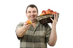 Stock Photo of smiling farmer offering one apple for you