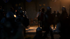 Medieval knights and warriors walk off illuminated stage at night Stock Footage
