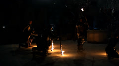 Performers in medieval clothes spit fire on stage in the night Stock Footage