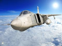 Military jet bomber su-24 fencer flying above the clouds. Stock Photos