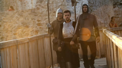 Three medieval warriors walk across small bridge Stock Footage