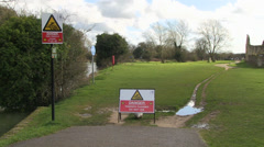 Warning flooded path sign by river thames in oxfordshire Stock Footage