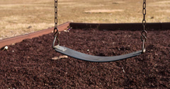 Empty playground swing going back and forth 4k Stock Footage