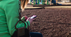 Girl on swing texting at playground 4k Stock Footage