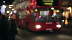 Traffic at night in london. red bus is passing by as nightlife in london cont Stock Footage