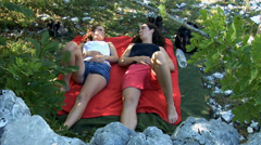 Two girlfriends lay on their backs in the nature and talk Stock Footage
