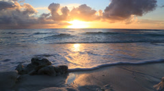 Waves lapping shoreline at sunset Stock Footage
