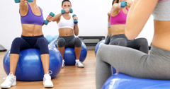 Fitness class sitting on exercise balls lifting hand weights Stock Footage